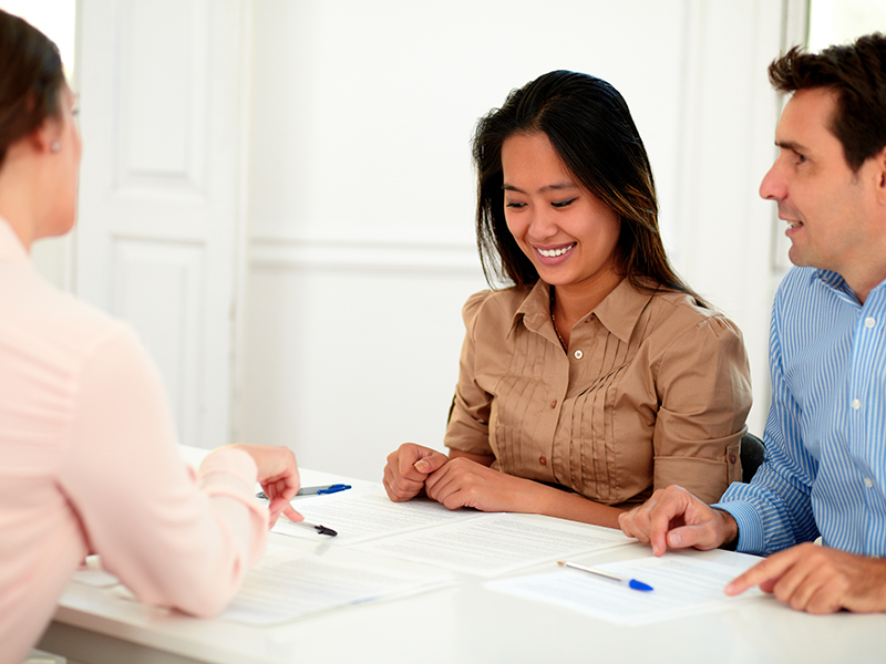 Portrait of young couple working with financial advisor while smiling and sitting on assistance workplace