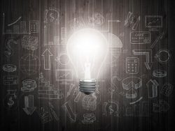 Glowing light bulb on wooden wall with drawing charts and