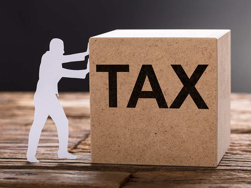 Closeup of paper man pushing tax wooden block on table against gray background
