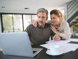 Couple calculating financial savings on internet